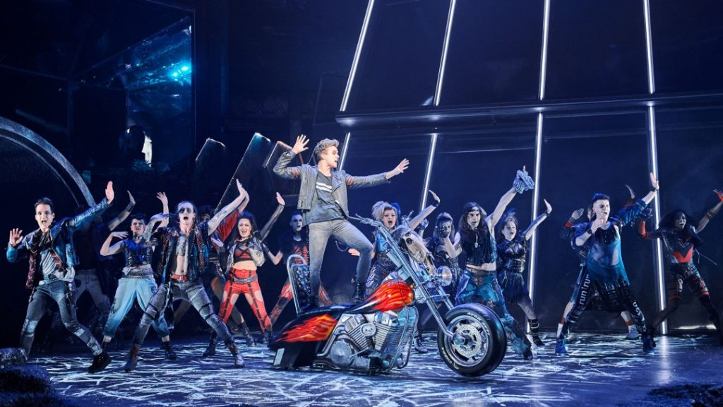 Scene from Bat Out of Hell The Musical: Strat is singing on top of a motorbike, with a group of dancers behind him.